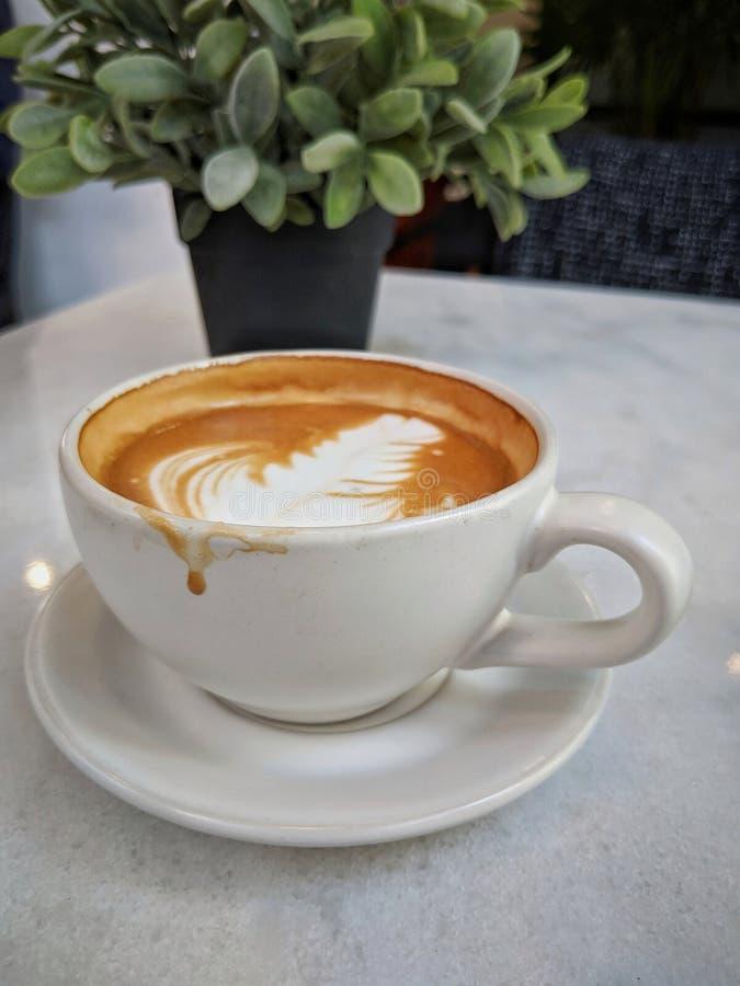 Ein Tasse Kaffee Latte auf einer weißen Marmortabelle, konzentrierend auf den Kaffeefleck auf der Schale nach Getränk stockbilder