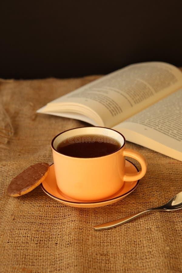 Ein Tasse Kaffee mit einem Buch stockfotografie