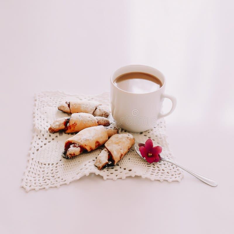 Ein Tasse Kaffee mit Hörnchen auf weißem Hintergrund Guten Morgen Frühstücks-Ebenenlage stockfotos
