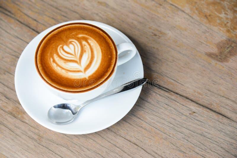 Ein Tasse Kaffee mit Lattekunst in der Herdform in der wei?en Kaffeetasse auf Holztischhintergrund stockfotografie
