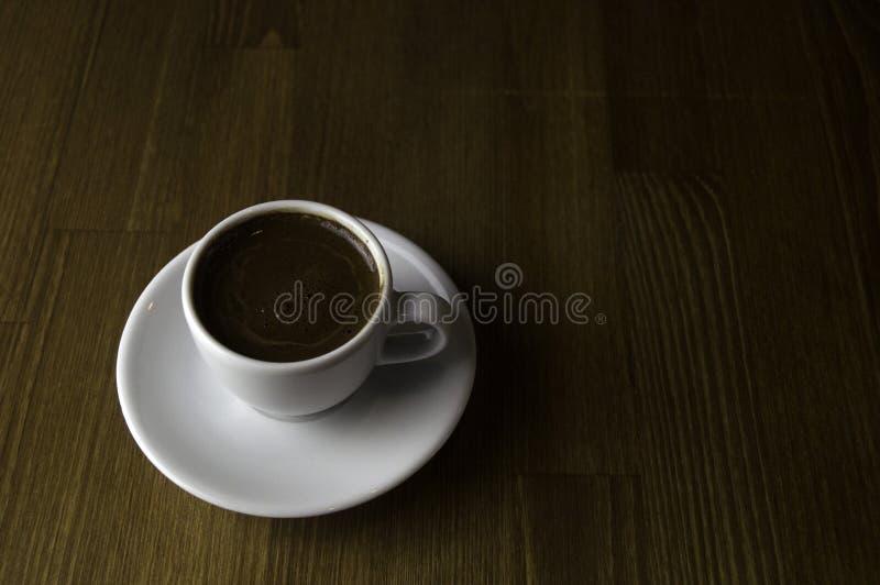 ein Tasse Kaffee mit Milch und brauner Tabelle stockfotografie