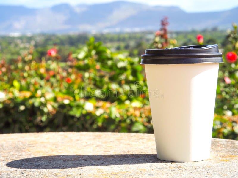 Ein Tasse Kaffee setzte an Felsentabelle auf den Rosengarten stockfoto