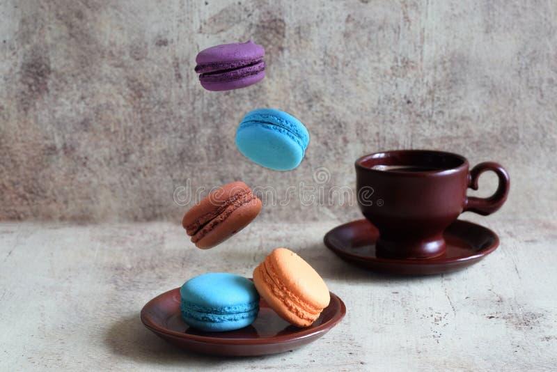 Ein Tasse Kaffee und bunten macaron Kekse, die auf eine Platte von einer Höhe fallen stockfotografie