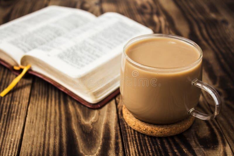 Ein Tasse Kaffee und eine Bibel auf hölzernem Hintergrund stockfotografie