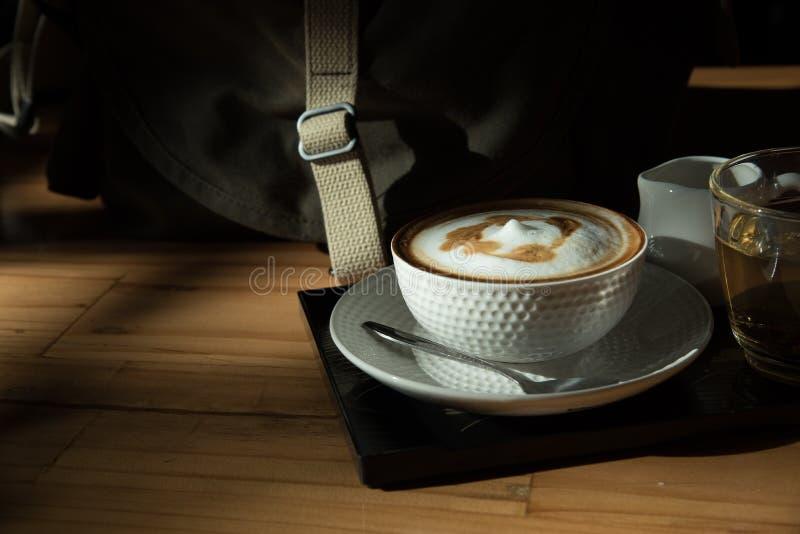 Ein Tasse Kaffee und eine Tasse Tee auf der hölzernen Tabelle stockbild
