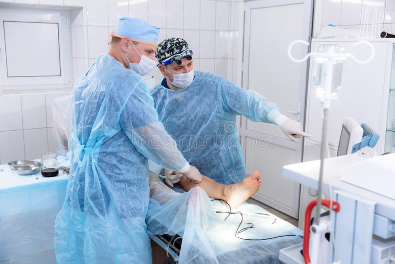 Ein Team von Doktoren im Operationsraum leitet medizinische Verfahren Chirurgen in der sterilen Kleidung arbeiten im Krankenhaus stockfotos