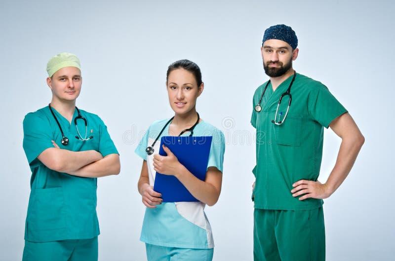 Ein Team von drei jungen Doktoren Das Team schloss einen Doktor und eine Frau, zwei Manndoktoren mit ein Sie werden herein sich s stockbild