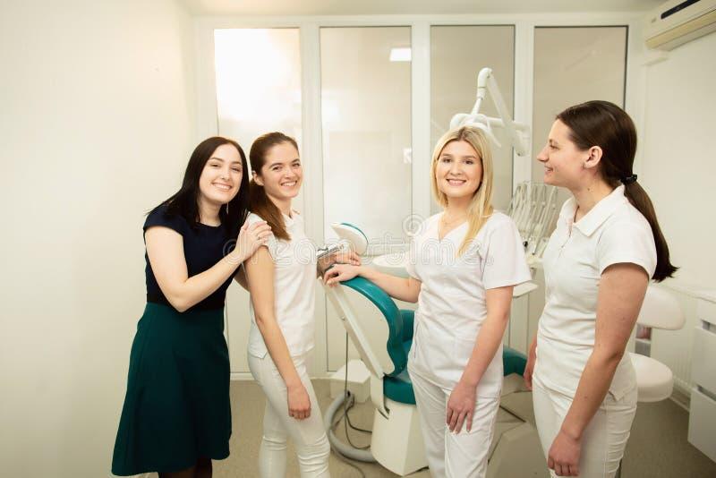 Ein Team von Fachleuten in einer zahnmedizinischen Klinik, werfend nahe der Ausr?stung auf lizenzfreie stockbilder