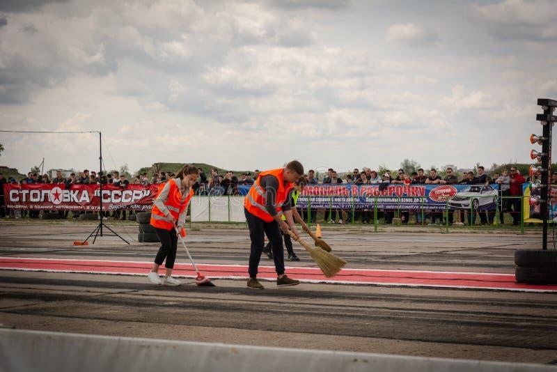 Ein Team von Reinigern in den orange Jacken säubert die Rennbahn auf Dragracingautos in Transnistrien stockbilder