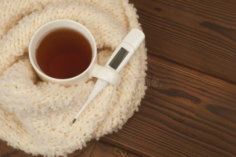 Ein Teebecher eingewickelt in einem weichen flaumigen gestrickten Schal, ein Thermometer auf einem hölzernen Hintergrund - das Ko stockfoto