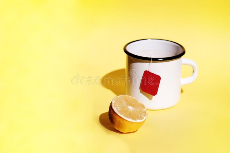 Ein Teebeutel in einem Metallbecher nahe bei einer Zitrone auf einem gelben Hintergrund lizenzfreie stockfotos