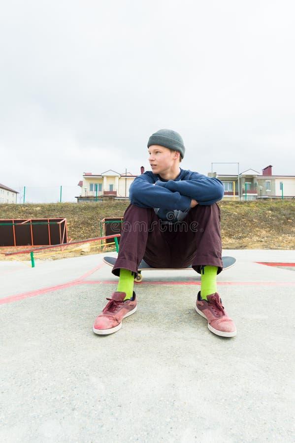 Ein Teenager sitzt auf einem Skateboard im Park Das Konzept des Freizeitzeitvertreibs für Jugendliche in der Stadt stockfoto