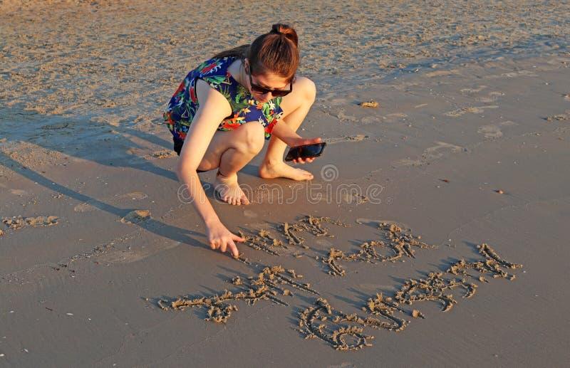 Ein Teenagermädchen schreibt auf dem Sand am Strand stockfotos