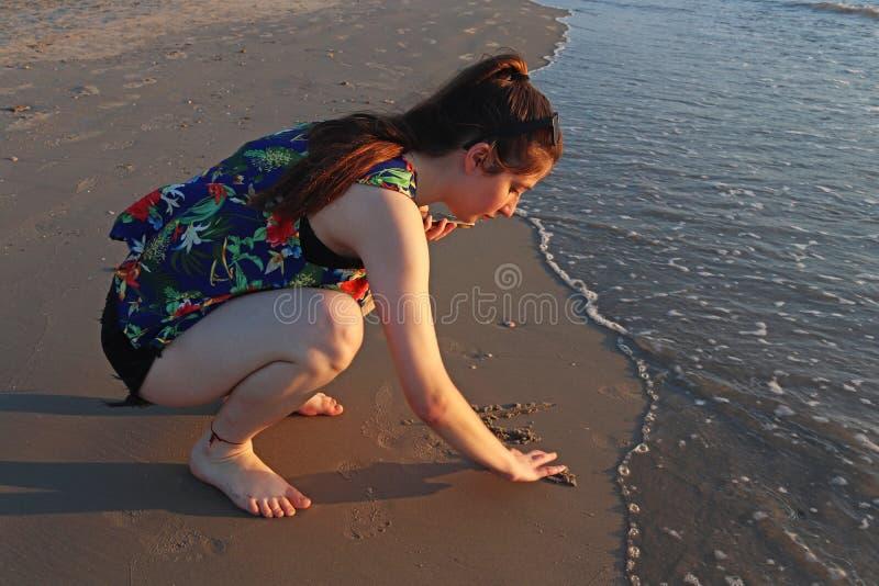 Ein Teenagermädchen schreibt auf dem Sand am Strand lizenzfreies stockfoto