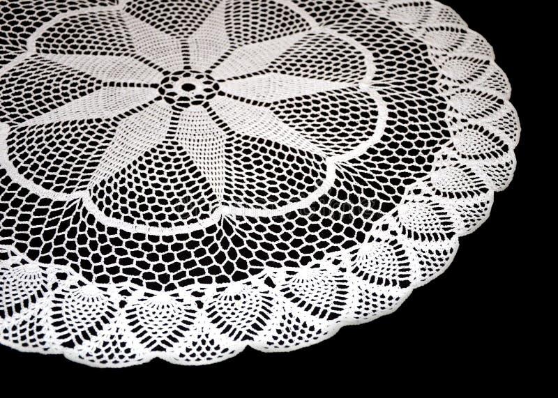 Ein Teil des lokalisierten gewirkten weißen Doily mit Muster mit Kegeln und Bögen ein schwarzer Hintergrund Runder dekorativer Ba lizenzfreie stockbilder