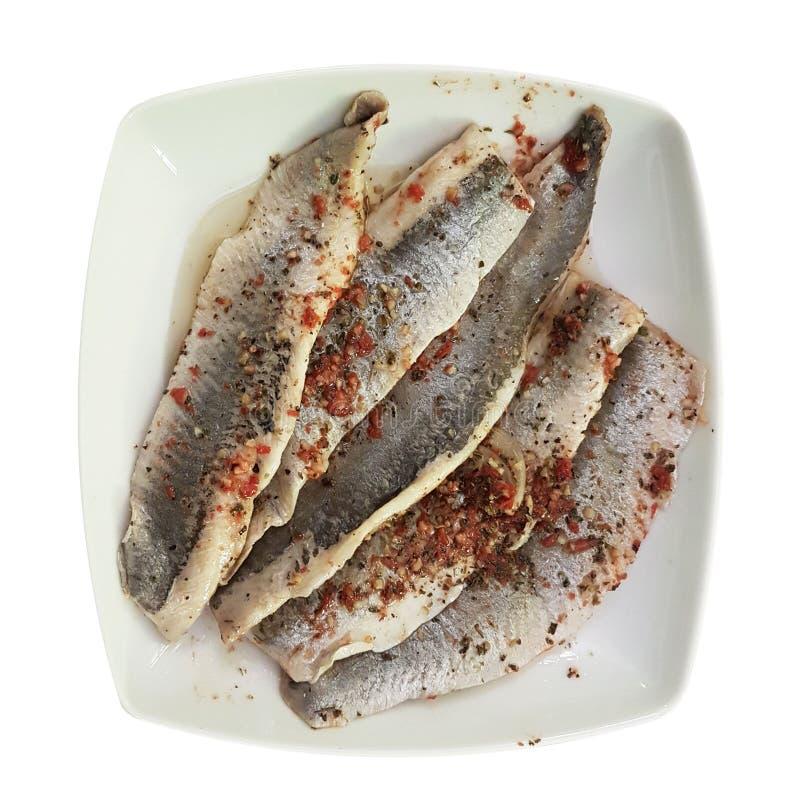Ein Teller des gesalzenen Fischfilets im Öl und der Gewürze auf einer Platte Nahrung auf einem weißen lokalisierten Hintergrund R stockfoto