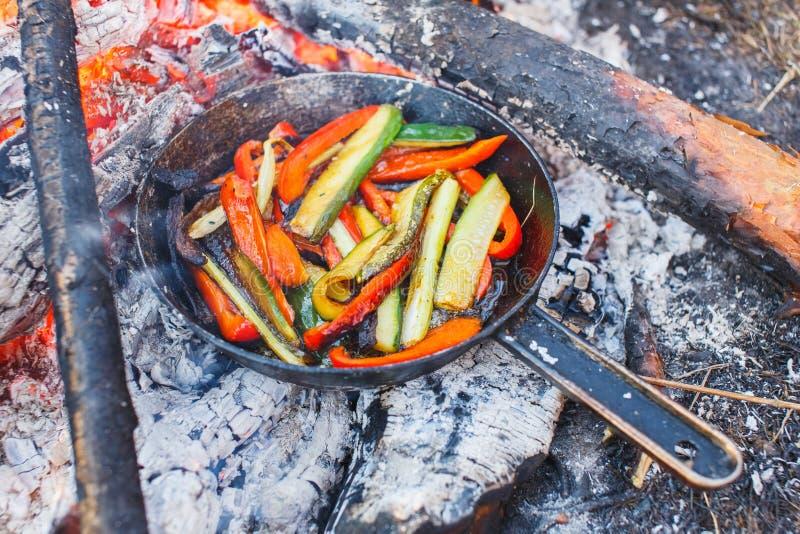 Ein Teller des roten grünen Pfeffers und der Gurken in einer Wanne auf einem Feuer stockbilder