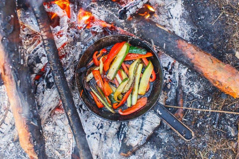 Ein Teller des roten grünen Pfeffers und der Gurken in einer Wanne auf einem Feuer stockfoto