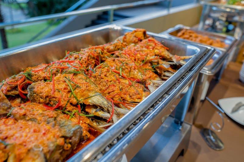 Ein thailändischer Nahrungsmittelfisch rühren sich gebraten in einer würzigen Soße in der Aluminiumdreieckplatte auf Linie Buffet lizenzfreies stockbild