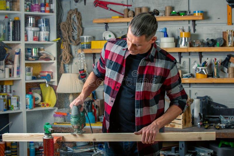 Ein Tischler arbeitet an Holzbearbeitung die Werkzeugmaschine Sägt Möbeldetails mit einer Kreissäge Prozess des Sägens von Teilen lizenzfreies stockbild