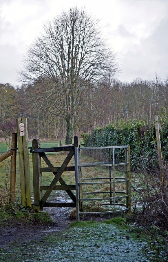 Ein Tor, das zu das Feld mit Baum, Büschen, Sträuchen und Schnee führt, bedeckte Gras in Kent England lizenzfreie stockfotos
