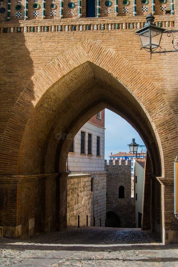 Ein Torbogen eines mudejar Artturms, der Altbauten und der Laterne an der Wand an der mittelalterlichen Stadt Teruel stockfotos
