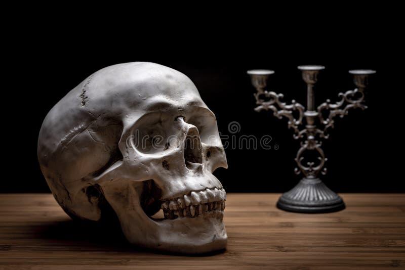 Ein Totenkopf auf einem Holztisch mit Kerzenständer lizenzfreies stockbild