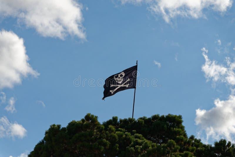 Ein Totenkopf mit gekreuzter Knochen, lustige Roger-Flagge fliegt von der Spitze eines Flaggenpfostens lizenzfreie stockfotos