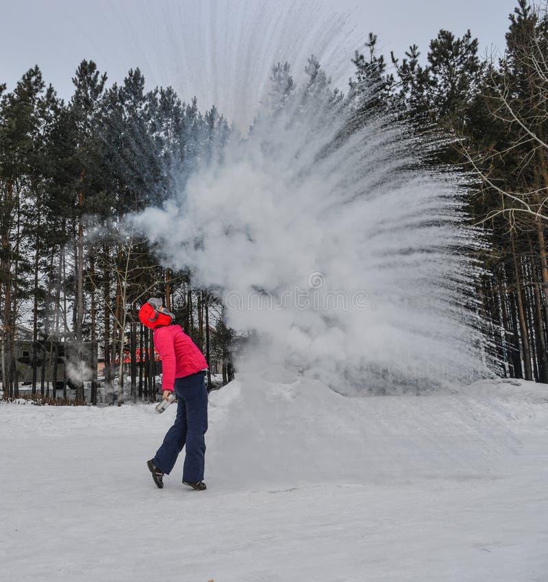 Ein Tourist, der Heißwasser am Winterpark wirft stockfotos