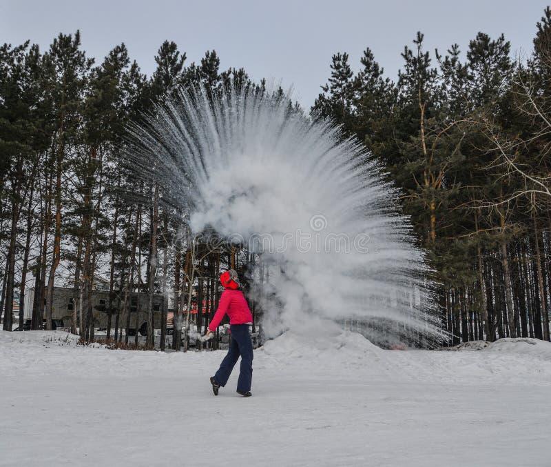Ein Tourist, der Heißwasser am Winterpark wirft stockfotografie