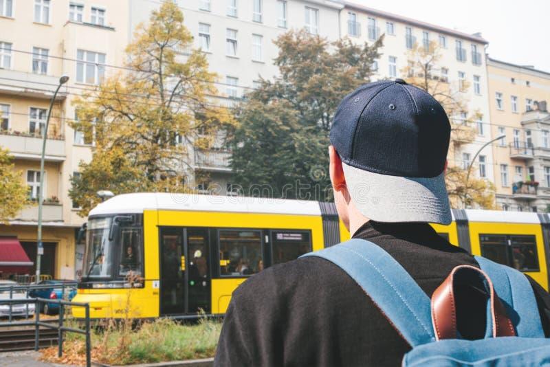 Ein Tourist in einer Baseballmütze mit einem Rucksack auf Berlin Street in Deutschland lizenzfreie stockfotos
