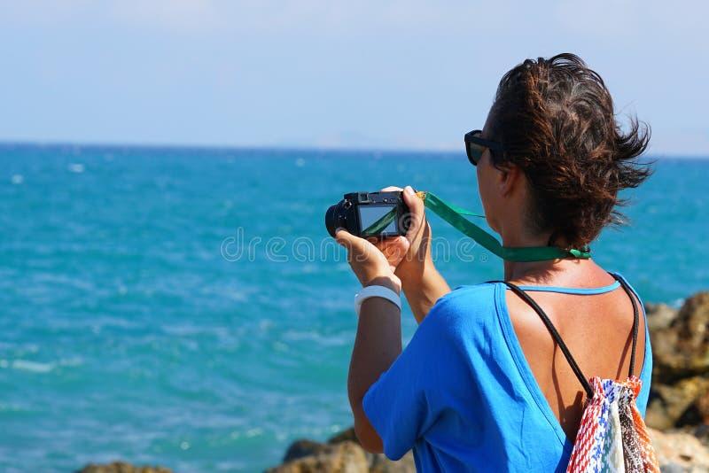 Ein Tourist fotografiert das Meer in Kreta stockfotografie