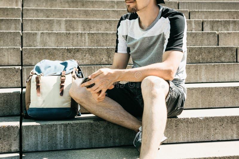 Ein Tourist oder ein Student sitzt auf der Treppe, den Resten und dem Gebrauch ein Handy stockfotografie