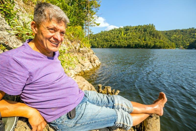 Ein Tourist sitzt auf der Bank des Yumaguzinsky-Reservoirs lizenzfreie stockbilder