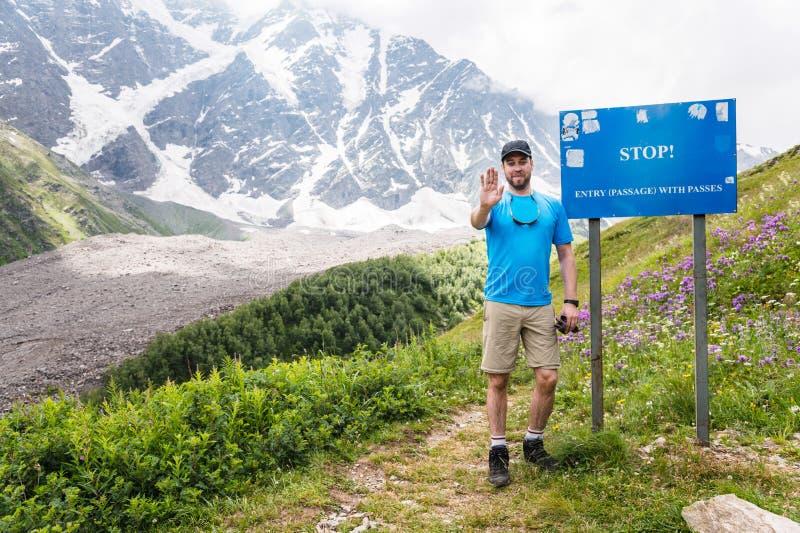 Ein Tourist steht ein Zeichen mit einem Stoppschild bereit lizenzfreie stockbilder