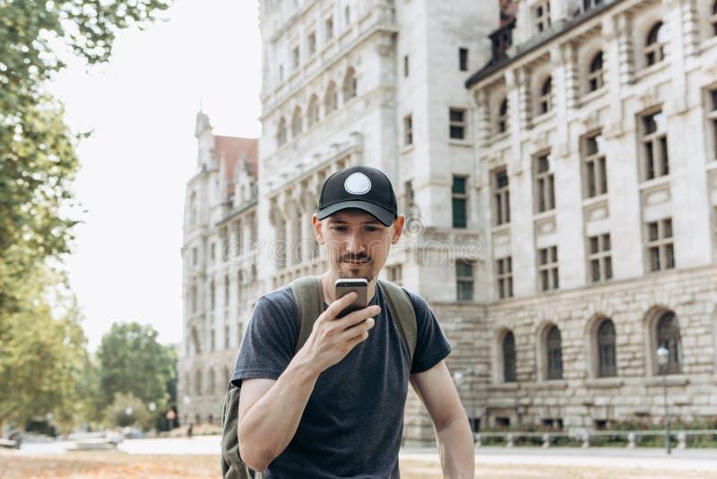Ein touristischer Mann oder ein Junge mit einem Rucksack benutzt einen Handy stockfoto