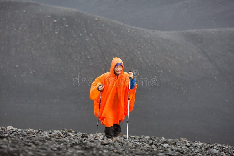 Ein touristisches Mädchen in einem orange Regenmantel mit Wanderstöcken klettert die Seite eines Schlafenvulkans lizenzfreies stockbild