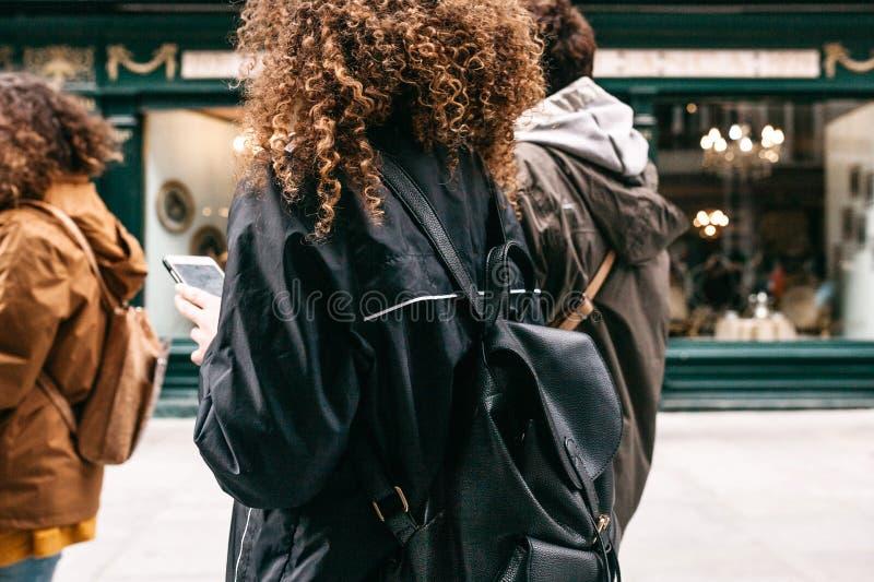 Ein touristisches Mädchen mit dem gelockten Haar mit einem Rucksack oder einem Studenten, die hinunter die Straße gehen und einen stockfotos