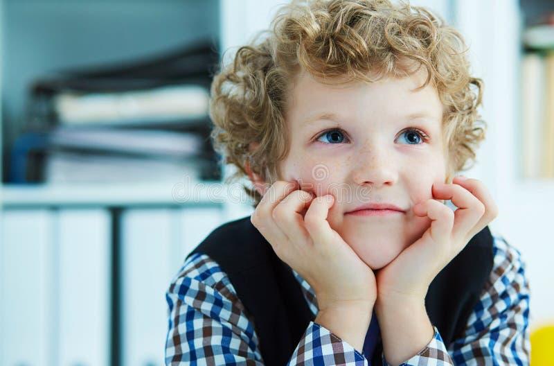 Ein träumender gelockter Junge hält seinen Kopf auf seinen Händen lizenzfreie stockfotos