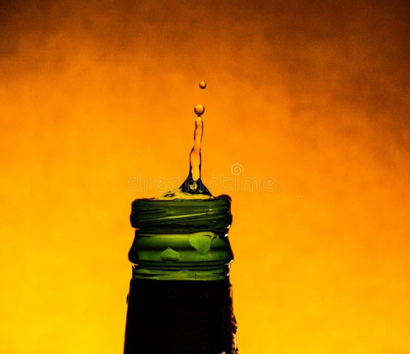 Ein Tröpfchen fällt in eine Flasche Wasser stockfoto