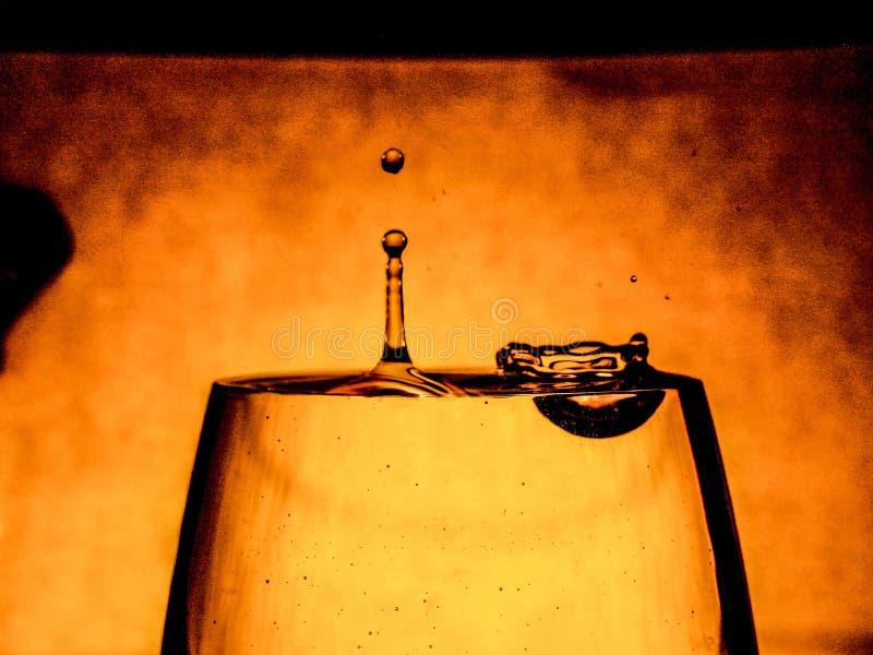 Ein Tröpfchen fällt in ein Glas Wasser lizenzfreie stockfotos