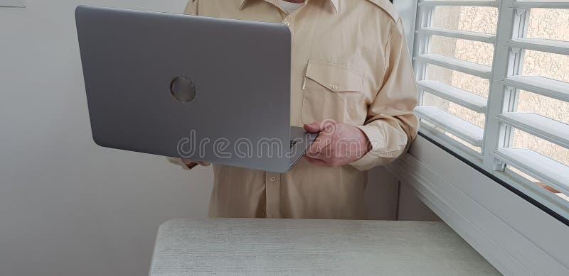 Ein tragendes hellfarbiges offizielles Hemd des Mannes steht in der Ecke stockbild