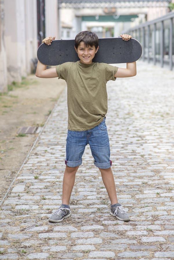 Ein tragendes Skateboard und ein Lächeln des Teenagers lizenzfreies stockbild