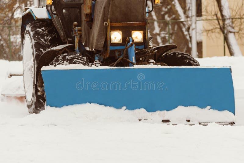 Ein Traktor mit Bürsten entfernt Schnee auf der Eisbahn lizenzfreie stockfotos