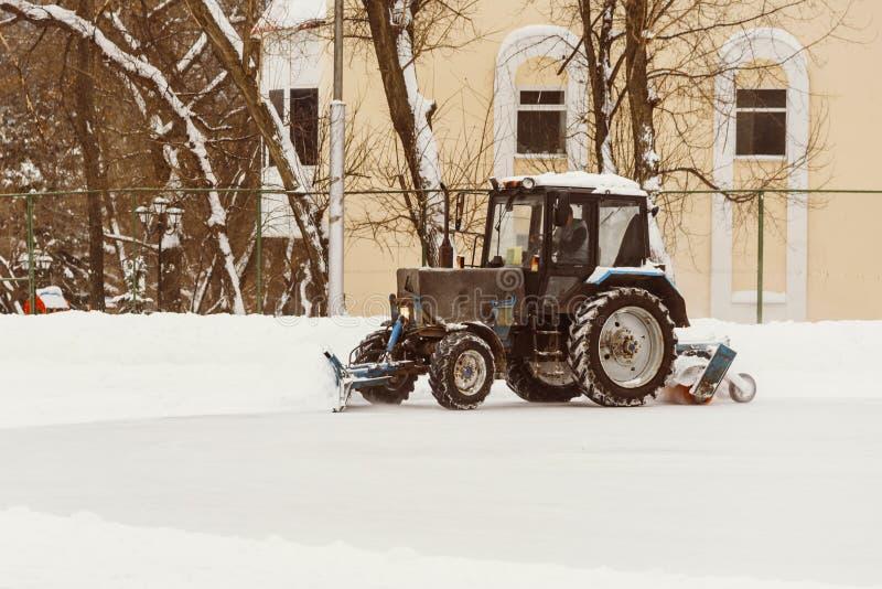 Ein Traktor mit Bürsten entfernt Schnee auf der Eisbahn stockbild