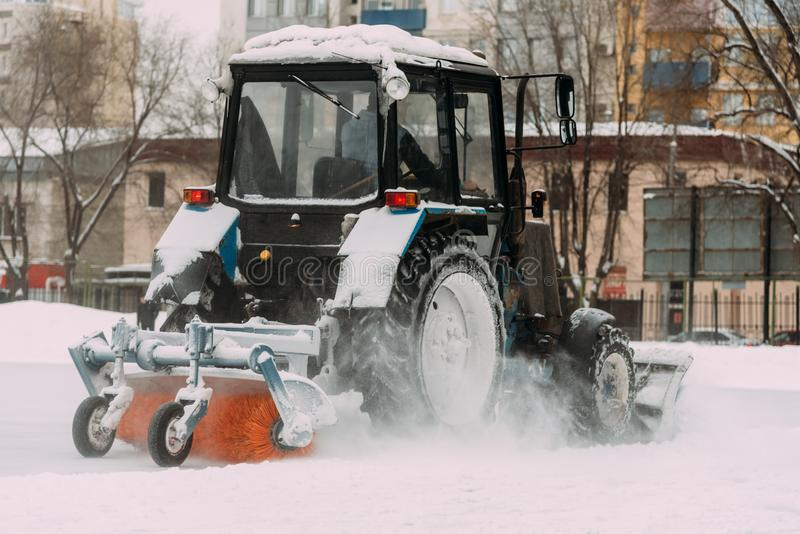 Ein Traktor mit Bürsten entfernt Schnee auf der Eisbahn lizenzfreie stockfotografie
