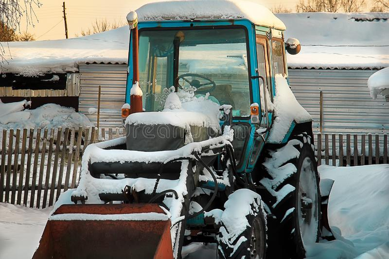 Ein Traktor mit den Ständen eines Spatens umfasst mit Schnee auf einem Bauernhof stockfotos