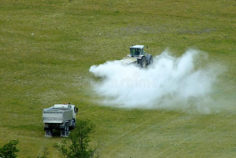 Ein Traktorbeginnsprühfeld mit Kalk/Insektenvertilgungsmittel/Schädlingsbekämpfungsmittel stockbilder