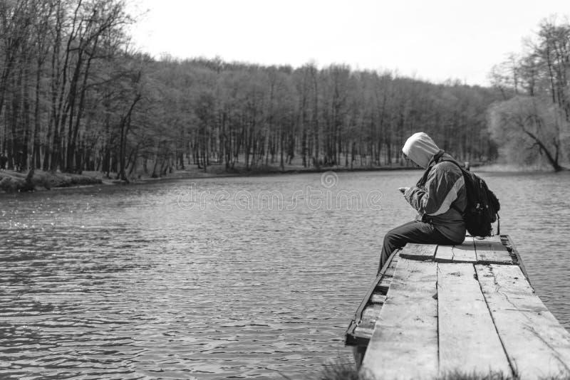 Ein trauriger Mann sitzt allein auf dem Pier durch den See Wald Schwarzweiss Haube auf seinem Kopf rucksack im Handgrifftelefon stockfotografie