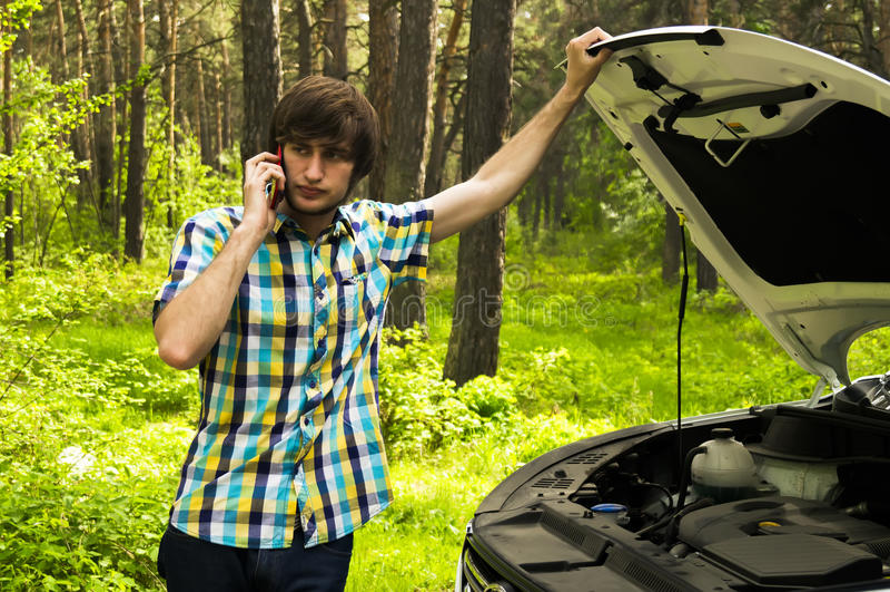 Ein trauriger Mann wartet auf Hilfe und nennt den Beistandsservice, weil sein Auto aufgliederte lizenzfreies stockfoto